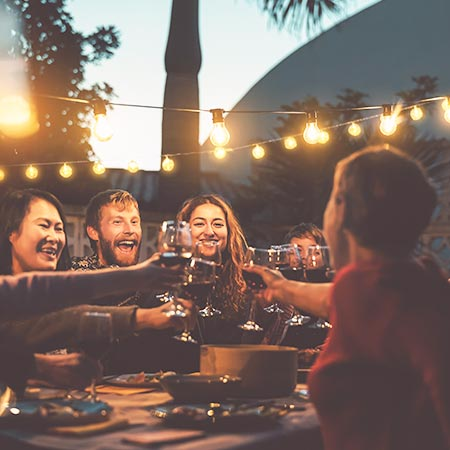 Vennegjeng som skåler og feirer i en hage